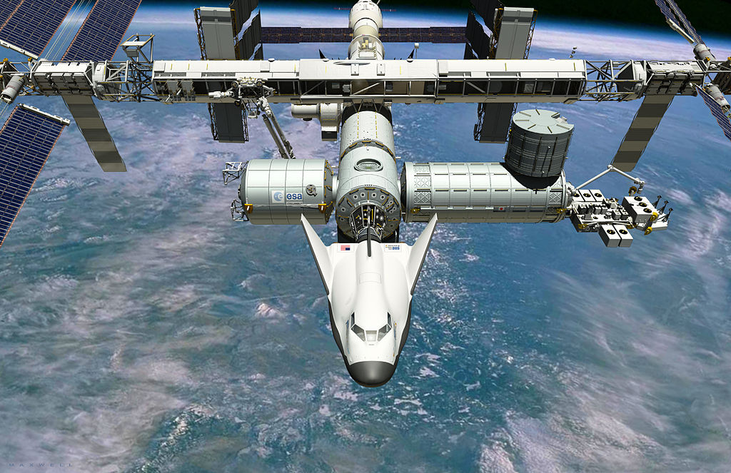 https://upload.wikimedia.org/wikipedia/commons/thumb/e/e0/Dream_Chaser_Docked_to_ISS.jpg/1024px-Dream_Chaser_Docked_to_ISS.jpg
