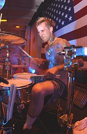 A man plays a drum kit in front of an American flag.