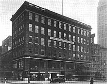 "A six-story dark brick building for retail stores (street level) and offices (above), a hundred feet long and about 30 feet deep, behind which the theater wing stretches to the left. Between the fourth and fifth floors, a big sign on the facade says ""Earl Carroll Theatre"" in capital letters. The right side of the office building has a marquee, which reads ""Just Because / A Melody Comedy"", over the theater entrance, which is through the office building; there's another marquee at the theater wing on the left. An old-fashioned automobile is parked in front of the building."