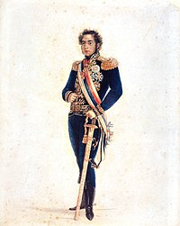 Colored full-length portrait showing a young man with curly hair and long sideburns who is wearing an elaborate gold-embroidered blue military tunic with gold epaulets and medals, blue trousers, black boots, a striped sash of office and gold belt, with his left hand resting on a sheathed sword