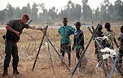 A French soldier, one of the international force supporting the relief effort for Rwandan refugees, adjusts the concertina wire surrounding the airport.