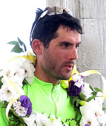 A man with parrot-green color athlete's attire, sunglasses on his head and a flower garland around his neck