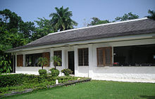 A white-washed bungalow with a lawn in front