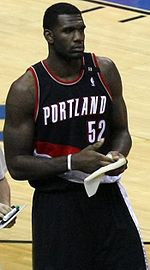 "A basketball player, wearing a black jersey with the word ""PORTLAND"" and the number 52 on the front, stands on a basketball court."