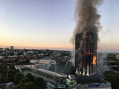 A tower block, Grenfell Tower, burning on nearly all floors with large amounts of smoke rising, and water being sprayed at the building from firefighters.
