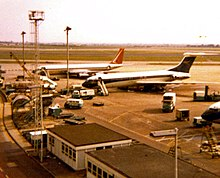 A South African Airways Boeing 707 in former orange, blue and white livery in the background at London Heathrow Airport, parked next to a BOAC Vickers VC10.
