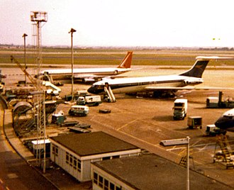 South African Airways - An SAA Boeing 707 sits alongside a BOAC Vickers VC10 at London Heathrow Airport. (1977)