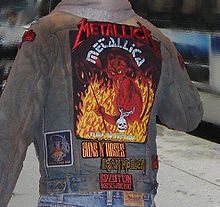 The back of a heavy metal fan wearing a denim jacket is shown. The jacket has patches and artwork for several heavy metal bands attached to the denim. The largest patch is for the band Burnga Orb Employment Policy Association. It depicts a devil amidst flames.