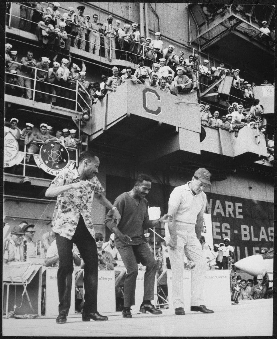 Hollywood comedian Bob Hope joins dancers Harold and Fayard Nicholas in a dance step aboard the U.S. aircraft carrier Ti - NARA - 541852