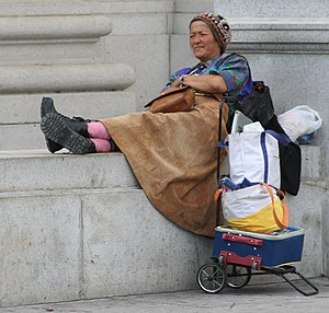 A homeless woman sitting at a monument in Wash...