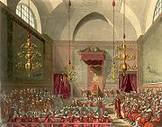 View of the House of Lords from the inside. Their lordships are sitting on three sides of a square, with the Speaker of the House, and the royal throne making up the fourth side.