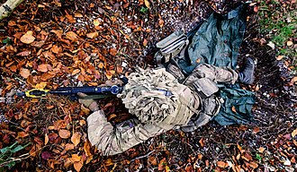 Shell scrape - A British soldier laying prone in a shell scrape during a training exercise in 2016