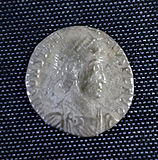 A smaller silver coin in the centre a head – still a fairly round coin but the inscription is not intact and there is no space between it and the rim