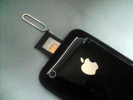 An iPhone 3G with the SIM slot open. The SIM ejector tool is still placed in the eject hole. - iPhone