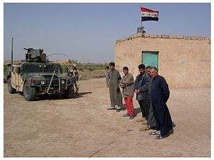 Civil-military operations - Iraqi farmers stand outside a rural school while a U.S. Army Civil Affairs team evaluates it for possible reconstruction funds (near Baghdad, April 2005).
