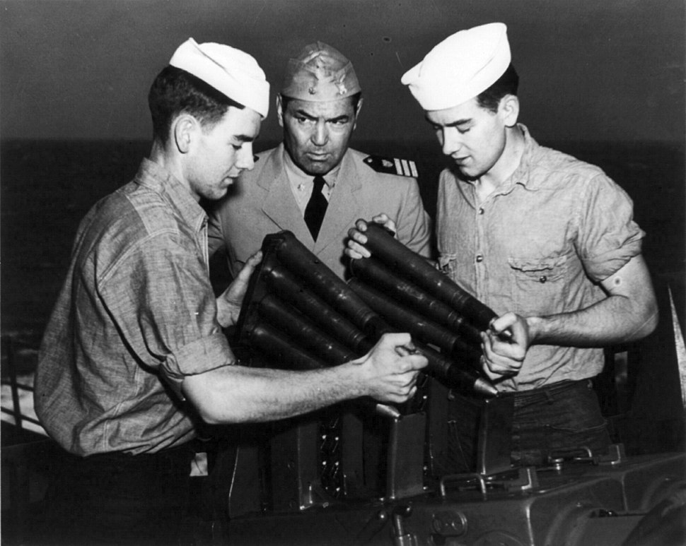 Jack Dempsey with USCG sailors loading weapon cph.3b08434