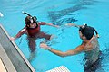 Jaeda Sichel, 18, swims with U.S. Coast Guard Petty Officer 3rd Class Ian Jobs, an aviation survival technician, at the Aviation Training Center swimming pool in Mobile, Ala., as part of her training to become 090707-G-UO910-117.jpg
