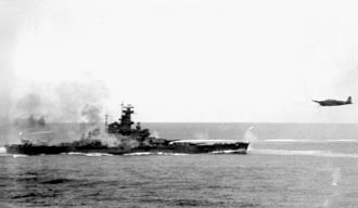 USS South Dakota (BB-57) - South Dakota fires at a Japanese torpedo bomber (right) during the Battle of Santa Cruz. The smoke around the battleship is from the ship's anti-aircraft guns.