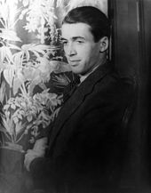 A black and white torso shot of Stewart in a dark suit, sitting in front of a flower-print curtain