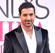 A smiling John Abraham, in a white shirt and black coat