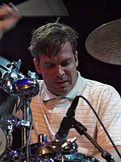 A close-up picture of a man playing drums