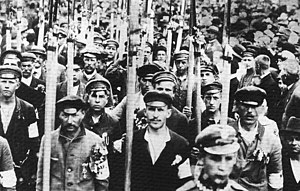 A black and white picture of a large group of men marching towards the camera, most of them dressed in civilian clothes and armbands, presumably in colours of the Polish national flag. The men carry long war scythes. To their right a large crowd of civilians.