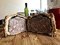 Large pork pie cut in half on a cutting bord made of wood.jpg