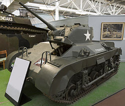A squat dark green tank in a museum, placed on a large green felt mat. There is a description board in front of it, and a grey divided wall to its rear. The tank's gun barrel is pointing towards the ceiling and its left-hand caterpillar tracks are visible, as well as several large handles on its hull.