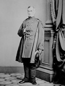 fotografia de corpo inteiro de uma guerra civil da era oficial do exército dos Estados Unidos.  Ele é colocado em um estúdio na frente de uma coluna decorativa com uma mão dentro do casaco.