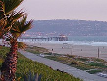 A photograph of a beach and a pier extending into the sea. In the foreground is a palm tree and a sidewalk, visible on the beach are a lifeguard station and a volleyball net, and on the horizon is a populated hillside.