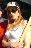 Woman in white knit blouse with hat, sunglasses and red hair
