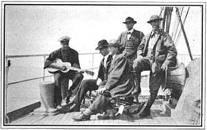 Claude Ewing Rusk - The four members of the Mazamas McKinley expedition being entertained by a musical member of the crew of the Tahoma. Right to left: A. L. Cool, Claude Ewing Rusk, Frank H. Rojec, and Joseph Ridley