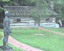 A log cabin with a statue and a tree in front