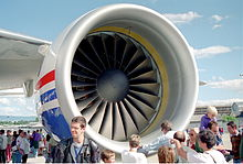 Crowd of people standing around a large engine of a Boeing 777