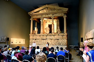An actor and actress performing a play in front of the Nereid Monument, Room 17, the British Museum, London NMT Automatic performing a play in front of the Nereid Monument.jpg