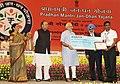 Narendra Modi presenting the award to Shri Ajith Gurunathan for suggesting the name 'Pradhan Mantri Jan Dhan Yojana (PMJDY)', in New Delhi. The Union Minister for Finance, Corporate Affairs and Defence, Shri Arun Jaitley.jpg