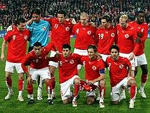 Photo d'une équipe de football posant sur deux rangs