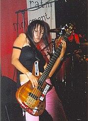 Femme brune, les cheveux devant les yeux, jouant de la guitare.
