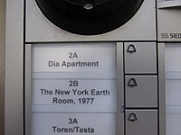 "An close up view of a building buzzer system showing a button for ""2A Dia Apartment"" and ""2B New York Earth Room""."