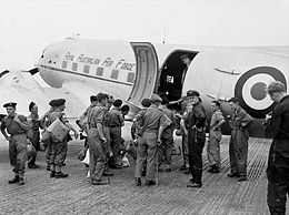 Uniformed personnel boarding a twin-engined transport plane