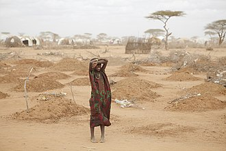2011 East Africa drought - A girl stands amid the graves of 70 children on the outskirts of Dadaab. The long desert journey to the relief camps has claimed many lives.