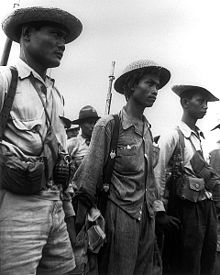 Three men, wearing uniforms and hats are standing and looking to the right. They are armed with grenades, guns, and have pouches. Other men can be seen in the background.