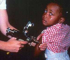 Jet injector - A health worker using a jet injector on a child