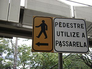 Pedestrian - A sign in Belo Horizonte, Brazil, directing pedestrians to an overpass for safe crossing.
