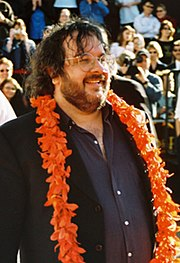 A photograph of Peter Jackson, a brown-haired, bespectacled man wearing a brown blazer, a blue shirt, and an orange lei