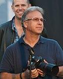 Phil Schiller holding a camera.
