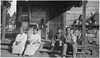 Fort Bidwell Indian Community of the Fort Bidwell Reservation of California - Group photograph sitting on the porch, at Fort Bidwell Reservation, c. 1924