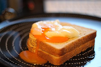 Poached egg - A single broken poached egg on 2 pieces of toast