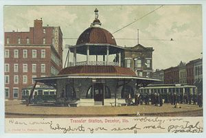 Decatur, Illinois - Trolley transfer station in its original location at the intersection of Main and Main streets; from a postcard sent in 1906