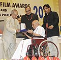 Pranab Mukherjee presenting the Swarna Kamal Award for Best Book on Cinema (Cinema Ga Cinema) to the Author, Shri Nandagopal, at the 61st National Film Awards function, in New Delhi. The Secretary.jpg